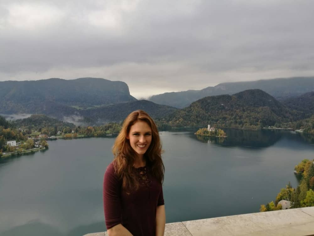 Maike sitting on the castle wall overlooking Lake Bled in Slovenia